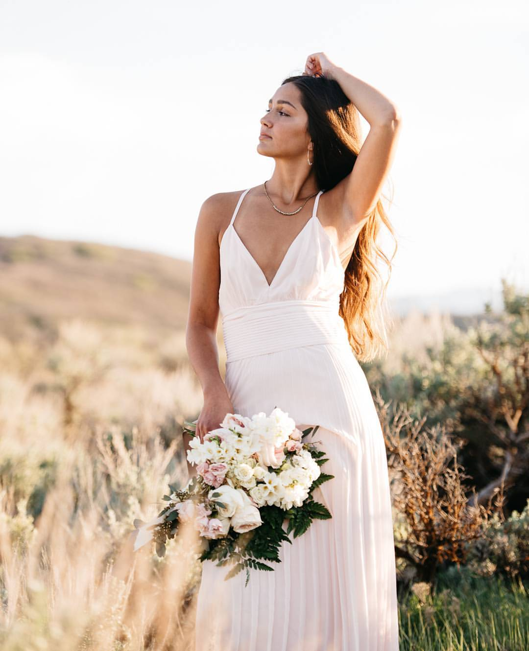 A bride posing with a bouquet out in a farm