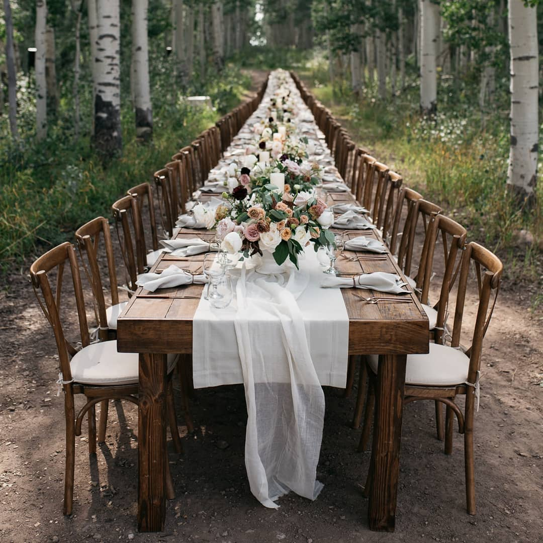 A banquet table decorated for an outdoor wedding reception