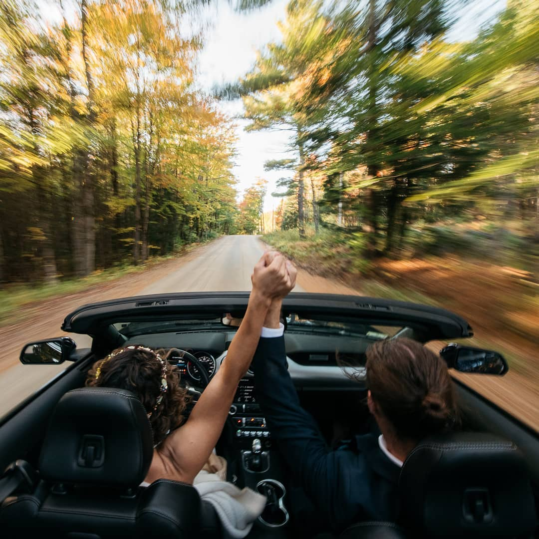 Bride and groom driving while holding each other's hands