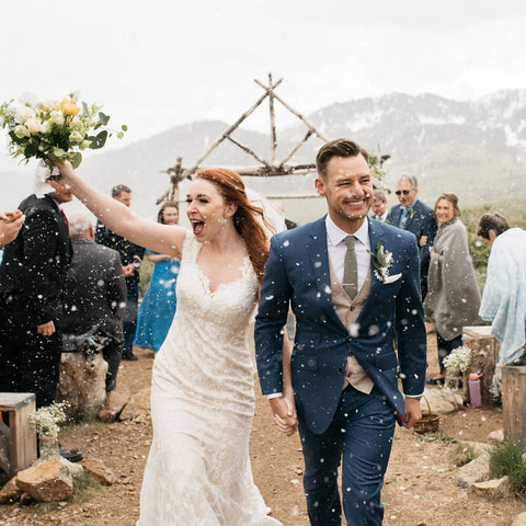 A bride and groom walk through two lanes of guest as they exit the ceremony