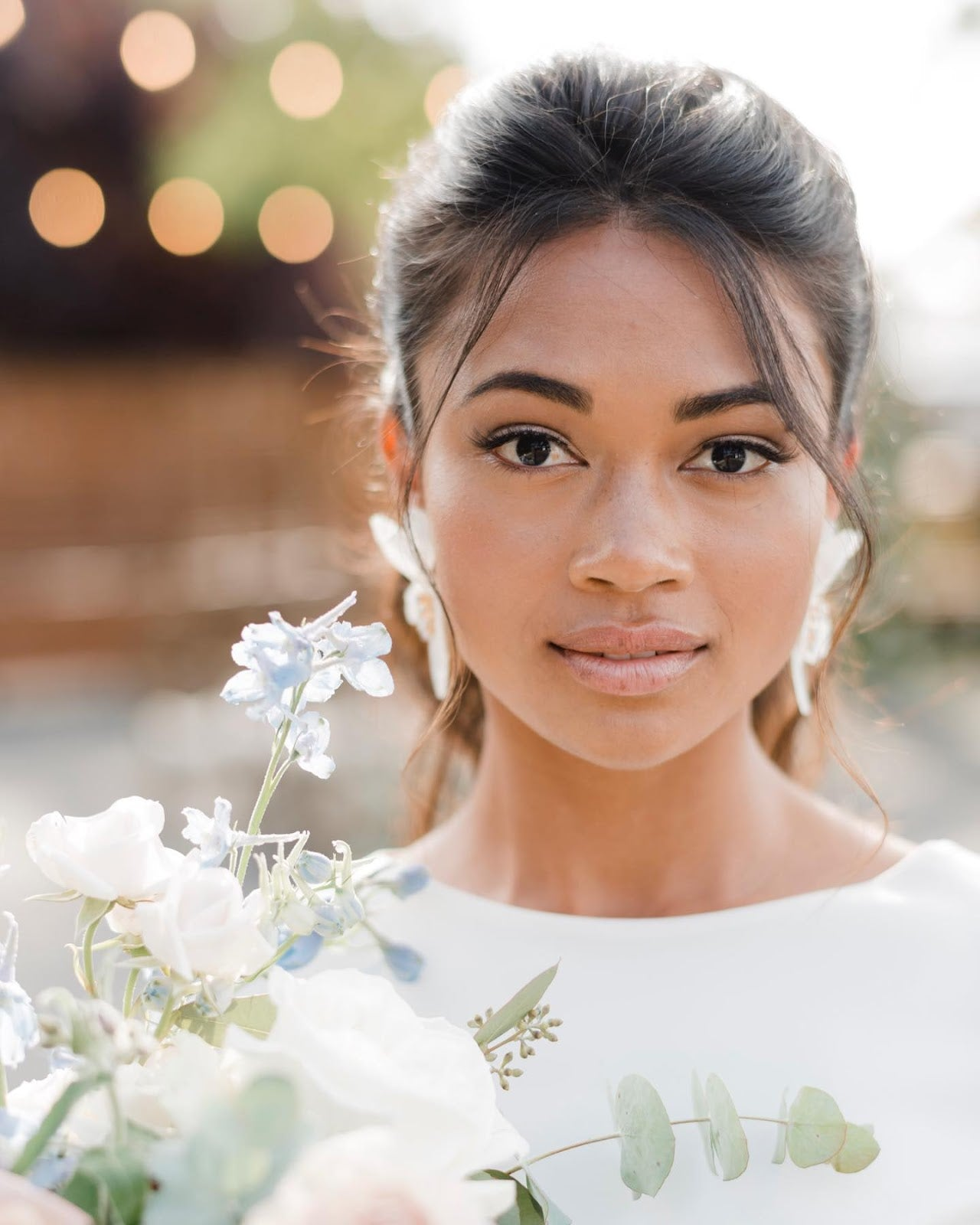 Portrait of a bride with a bokeh background and bouquet at the side