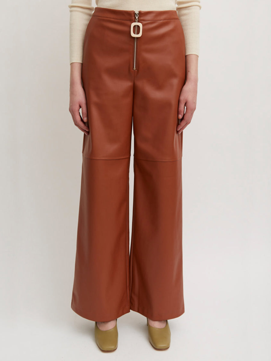 AÉRYNE CITRINE TROUSERS is a faux leather trousers in a straight fit, side pockets. Horizontal cutline detail and rectangular zip puller.