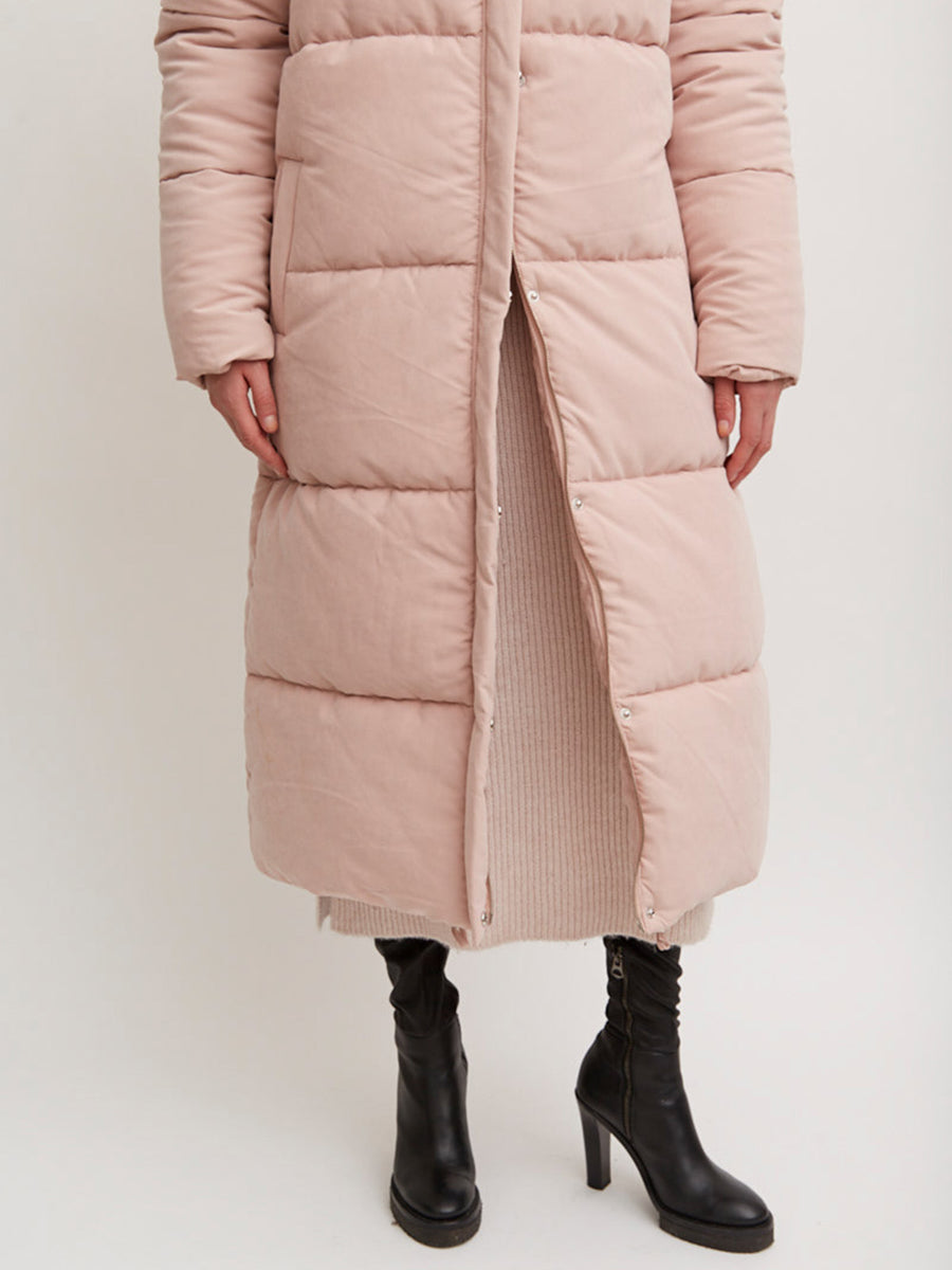 AÉRYNE IRON JACKET is a light pink padded puff coat with peach skin surface and high neck. Front pockets and draw string with pullers at bottom hem.