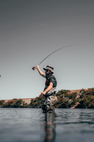 a fisherman casting a fishing rod into a lake, while wearing a bucket hat and uv protective clothing