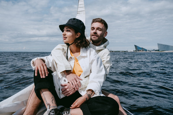a couple sitting on a boat on the ocean, the woman wearing a bucket hat and sun protective clothing, the man with his arms around her