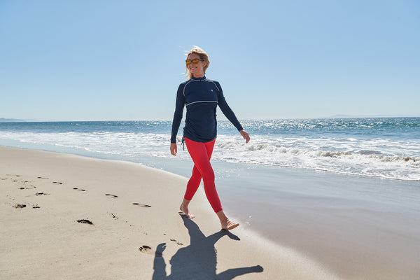 Woman walking on the beach wearing Coolibar sun protective clothing from UVwise