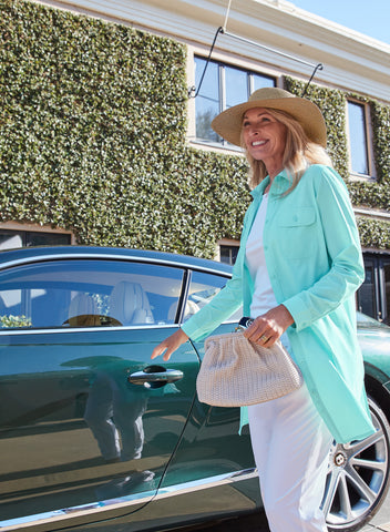 woman getting into a car wearing upper and lower body sun protective clothing