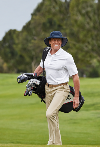 man walking on golf course green with golf clubs and wearing upper and lower body sun protection