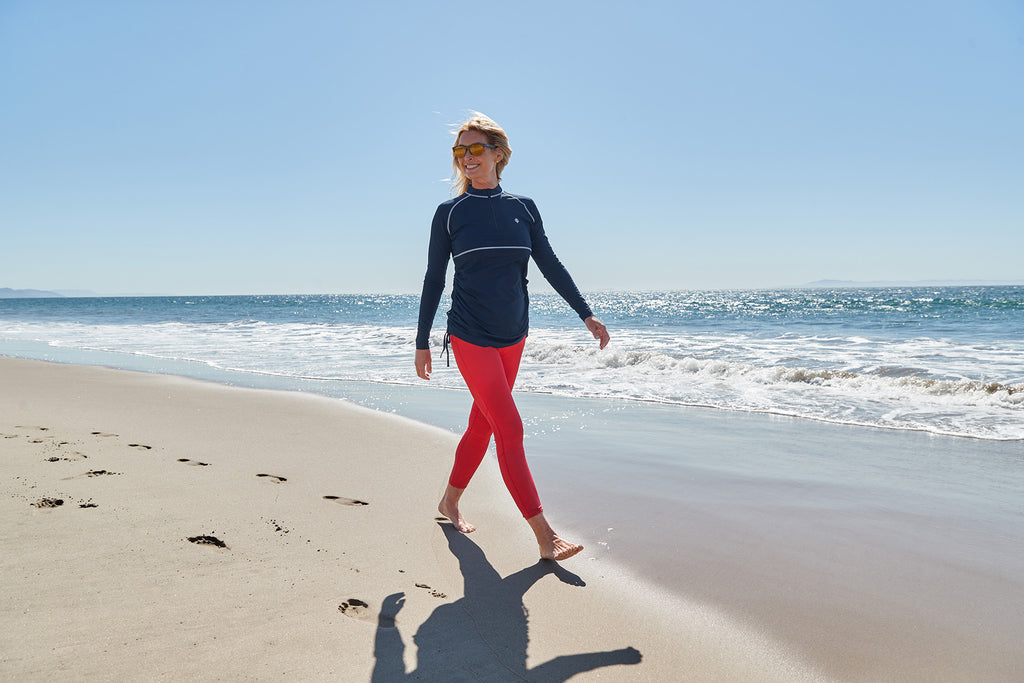 woman walking on the beach wearing upper and lower body sun protection from UVwise