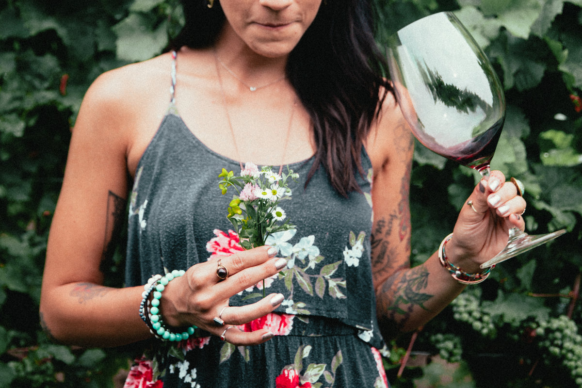 Beautiful woman standing in vineyard holding flowers in one hand and a glass of red wine. We can see that she is sipping the wine in such a way that she is feeling the taste and texture. She may or may not be a Sommelier, but it is unknown.