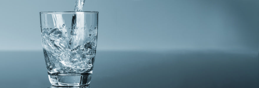 Glass of water being filled against a blue background.