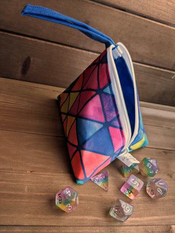 A zippered bag in the shape of a D4 with a loop handle sits on a wooden background with pastel rainbow dice with sparkles and silver numbers.