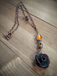 This brass necklace features a sculpted brass rose and a yellow glass bead suspended in a brass decorative component.