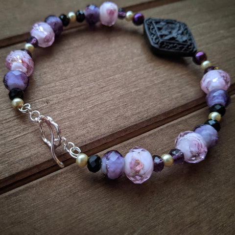 A bangle made with pink, purple, black, and white glass beads as well as a black carved stone bead.