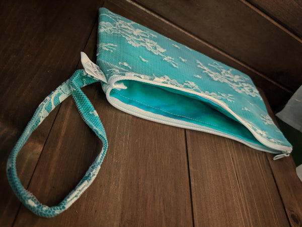 A zippered rectangular bag made with teal fabric under white Chantilly lace and a matching wrist strap sits on a wooden background.