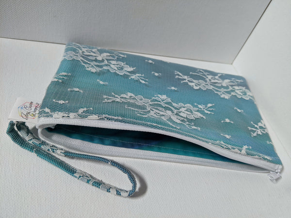 A zippered rectangular bag made with teal fabric under white Chantilly lace and a matching wrist strap sits on a white background.