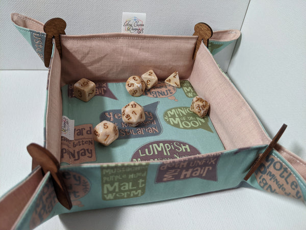 A fabric dice tray with peach linen print on one side and Shakespearean insults over a mint background sits with wooden clips in the corners on a white surface. Inside are marbled golden brown dice.