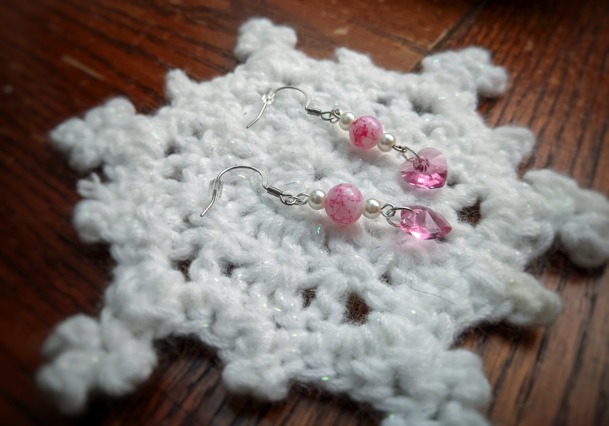 Dangling silver earrings feature pink marbled glass beads, white glass pearls, and pink crystal hearts.