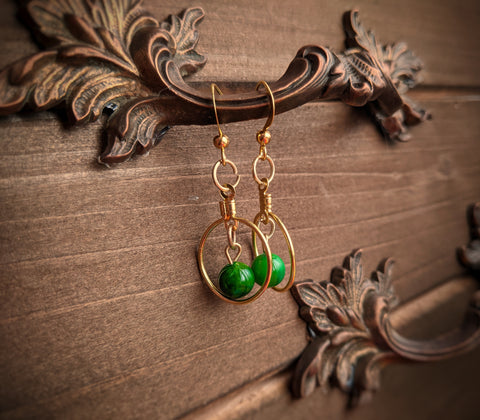 Golden brass earrings made with green glass beads dangling inside small hoops hangs on a brass handle.