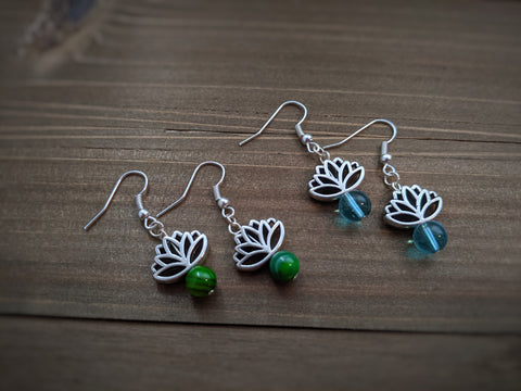 Silver lotus flower earrings with blue and green glass beads sit on a wooden background.