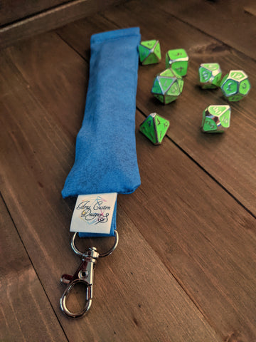 A long, skinny bag made with blue fabric, a squeeze opening, and a keychain clip at the top.