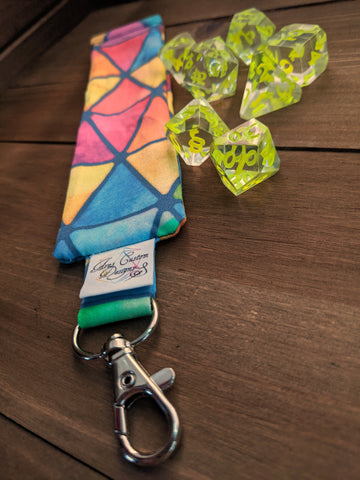 A long, skinny bag with a keychain clip at the top and a squeeze open sits on a white background. It's made with colorful watercolor triangle print fabric sits on a wooden background with clear dice with neon green numbers.