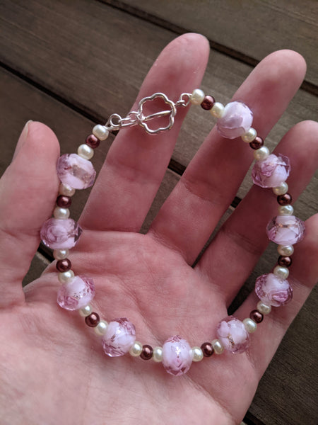 A beaded bracelet with pink floral glass beads and brown and cream glass pearls sit in Aras' hand.