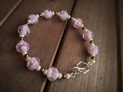 A beaded bracelet with pink floral glass beads and brown and cream glass pearls sit on a wooden surface.