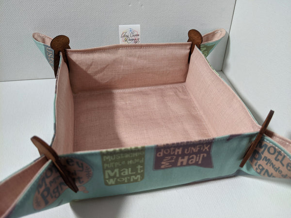 A fabric dice tray with peach linen print on one side and Shakespearean insults over a mint background sits with wooden clips in the corners on a white surface.
