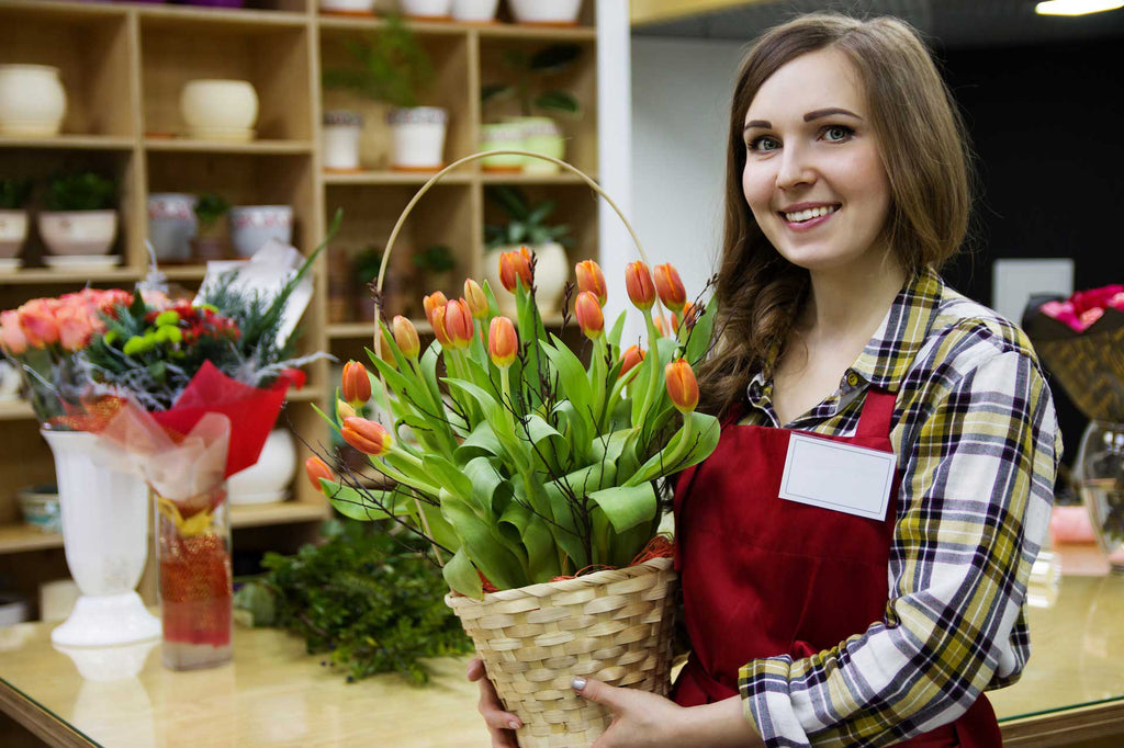 Girl working in store holding basket of flowers