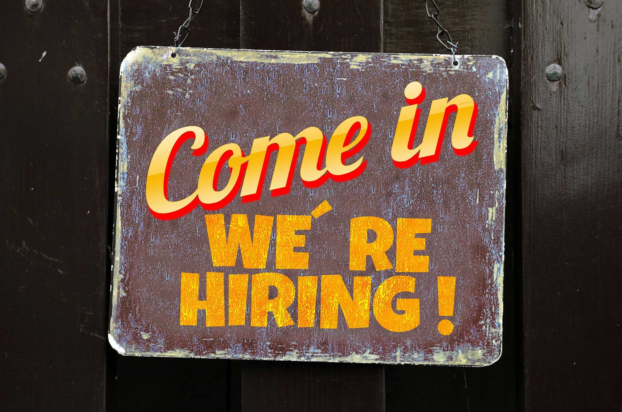 """Rustic """"We're hiring"""" sign welcoming employment applicants to the inquiry page"""