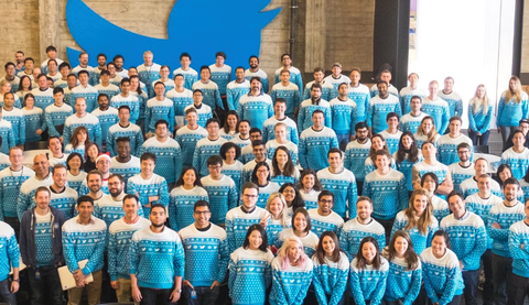 A large amount of the Twitter team gathered in front of the Twitter logo