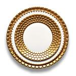 A place setting alternating white and gold plates sculpted with Aegean wave motif.