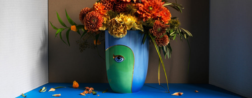 Bright bue and green two-tone porcelain vase with blue and gold eye decoration, filled with orange flowers.