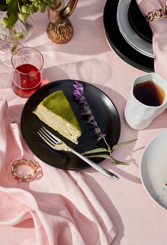 Al fresco tabletop set with pink table linens, black and white dinnerware and brass candlestick holders.