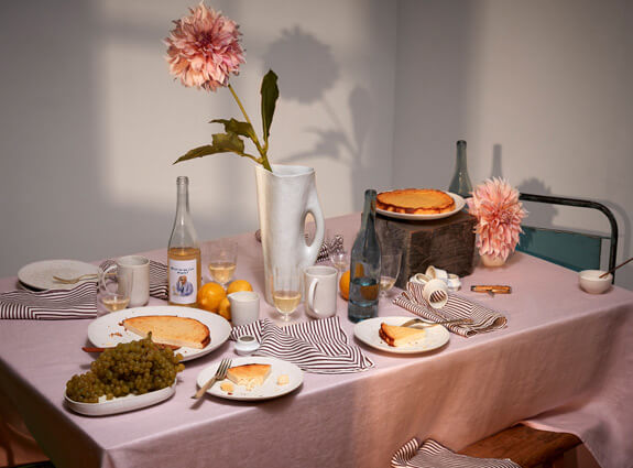 Tabletop set with pink tablecloth, wine and ecru striped napkin, stone Timna pitcher holding a pink flower, and cheesecake on stoner Terra dessert plates.