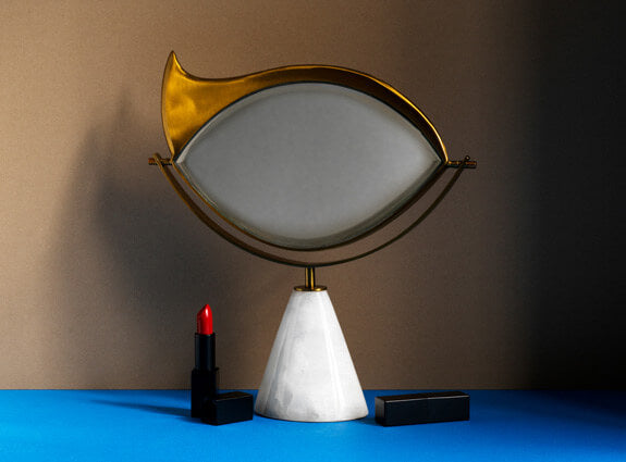 Decorative vanity mirror with brass eye-shaped mirror frame and conical marble base.