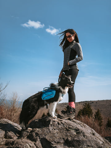 Kristina and Draco the border collie standing on a rock.