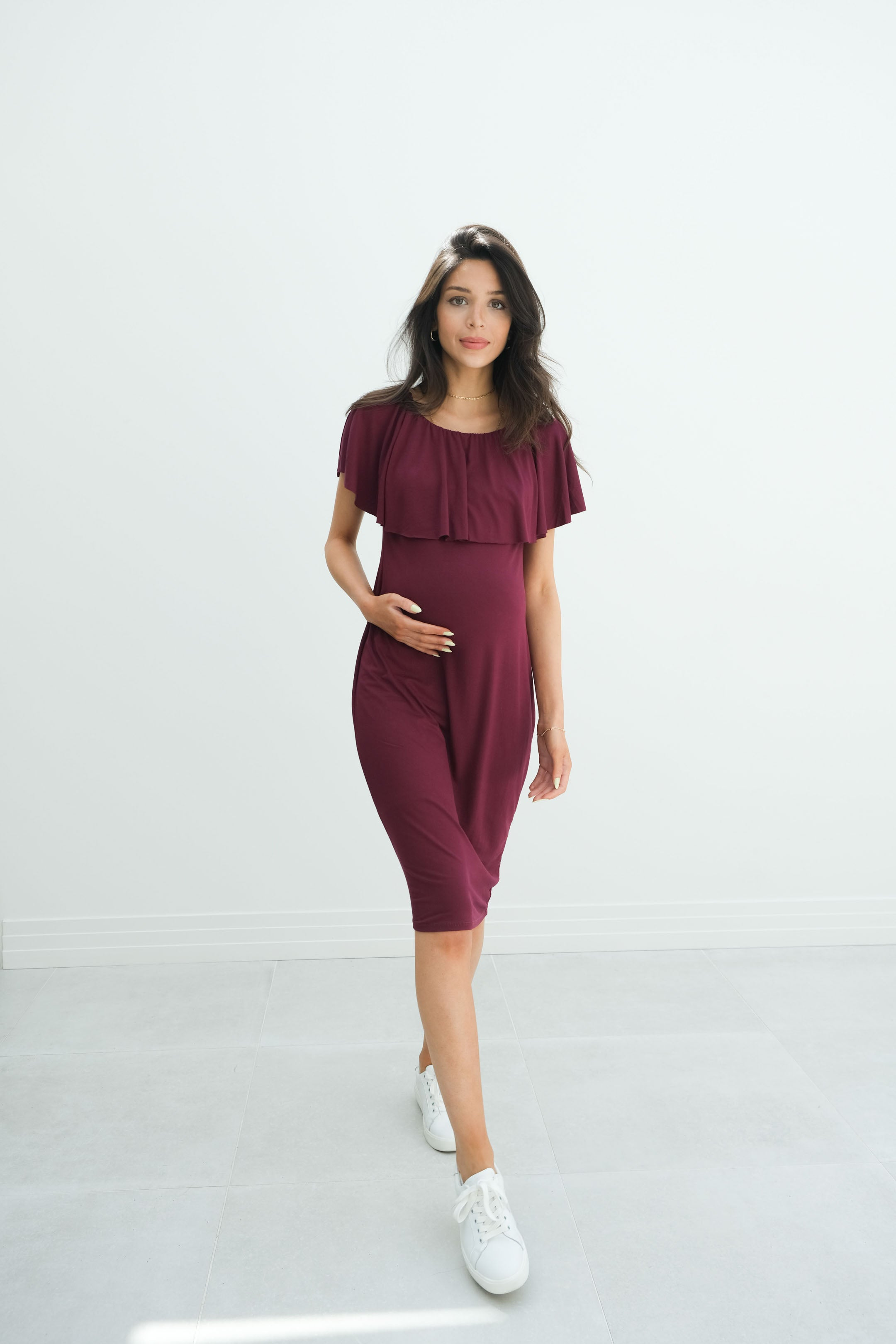 a lady wearing a burgundy pregnancy dress called melody