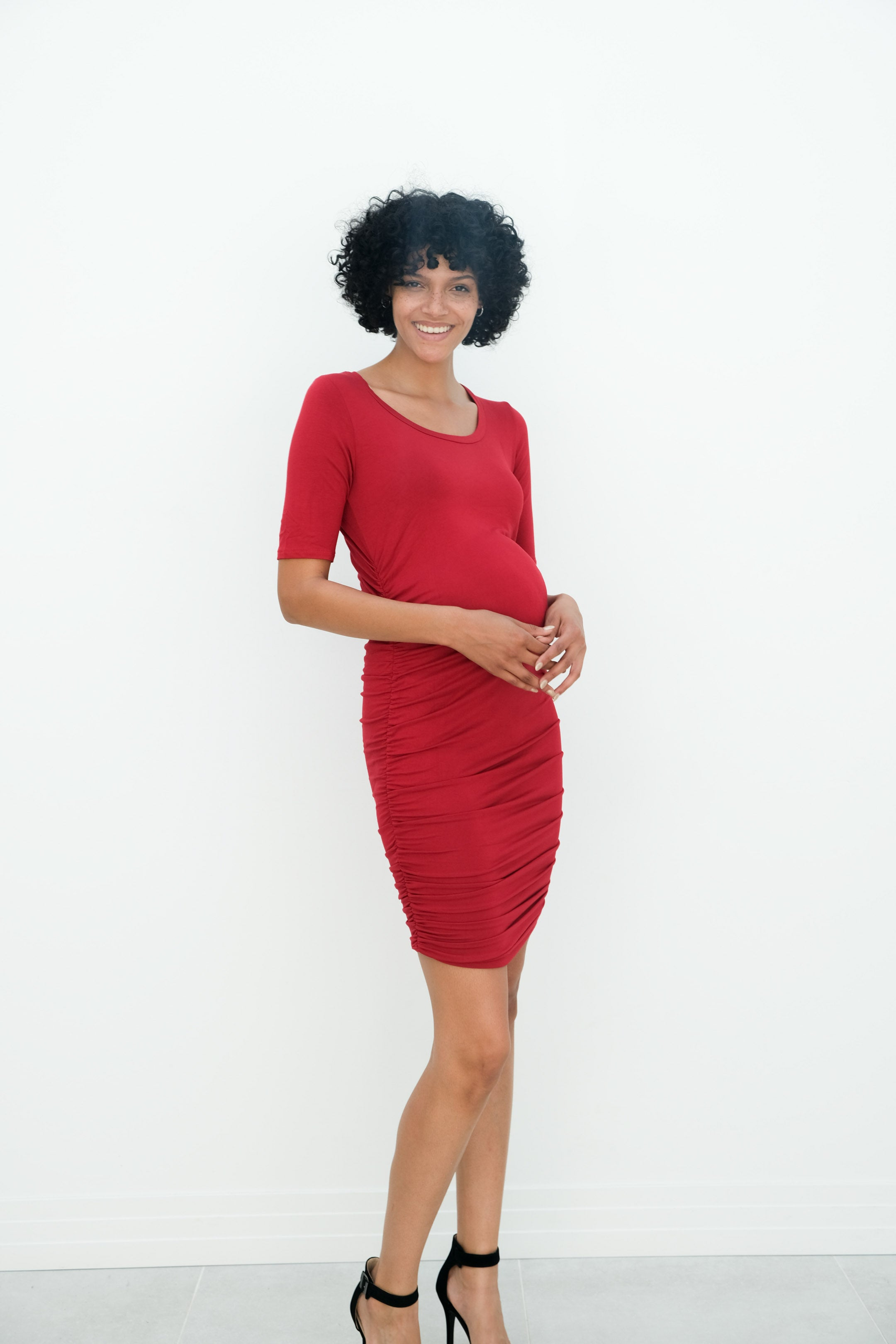a woman wearing the athena pregnancy gown