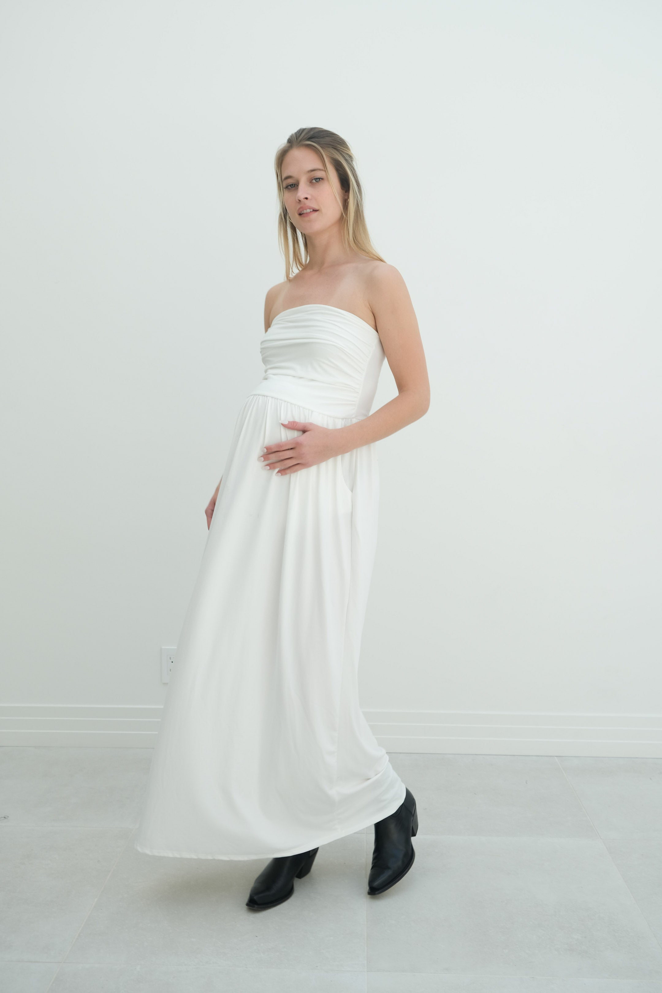 a pregnant woman wearing a white strapless casual maternity dress