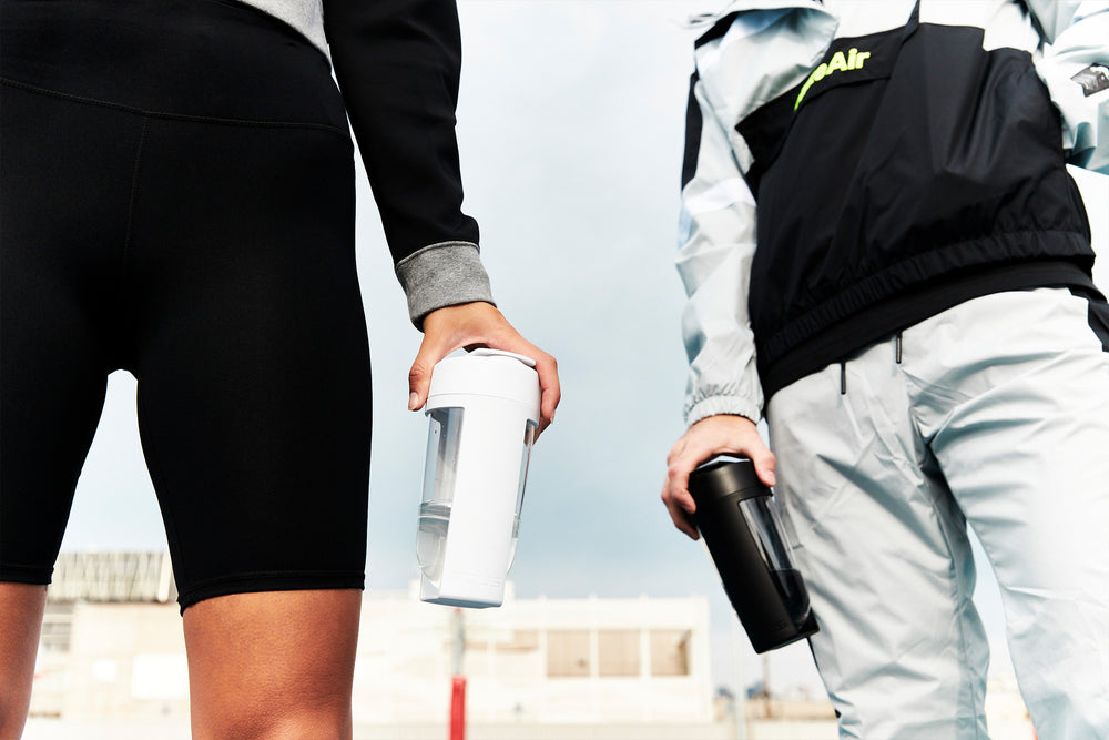 mous fitness bottle in black and white held in nike streetwear