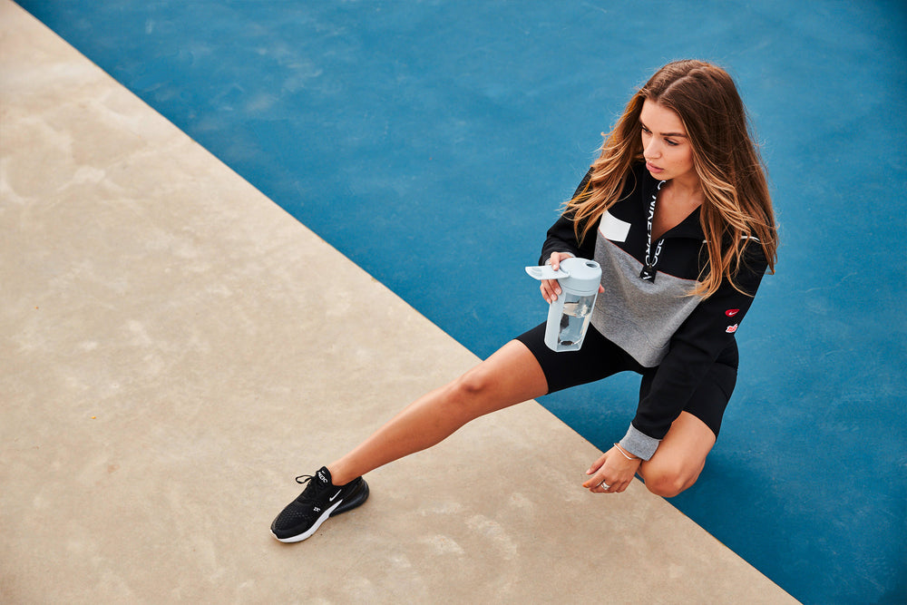 mous fitness bottle with lady wearing nike streetwear on basketball court