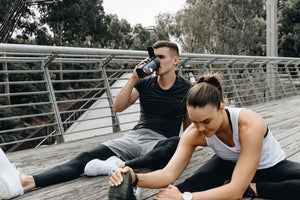 drinking from mous shaker bottle black in park working out with training partner