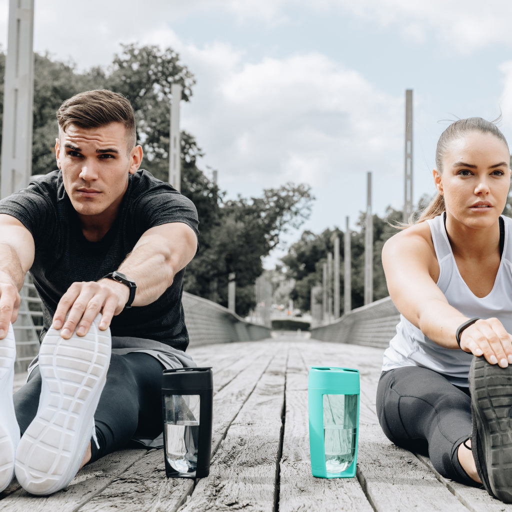 two people stretching with black mous shaker bottle and teal mous shaker bottle