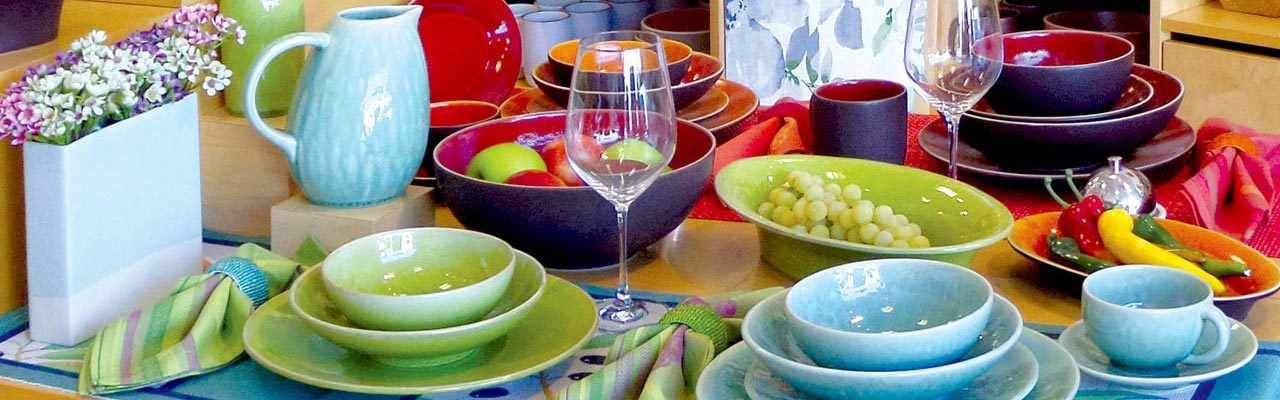 A tabletop arrangement of colorful stoneware from Jars Ceramics of Provence, France.