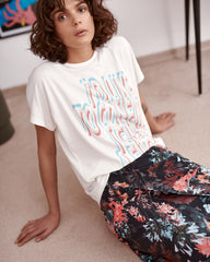 T-shirt with printed slogan worn with floral skirt close up