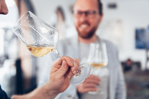 A person tasting wine from a glass