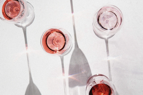 A top-down view of five wine glasses with red stains.