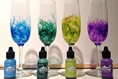 Four wine glasses behind four bottles of colored alcohol ink.